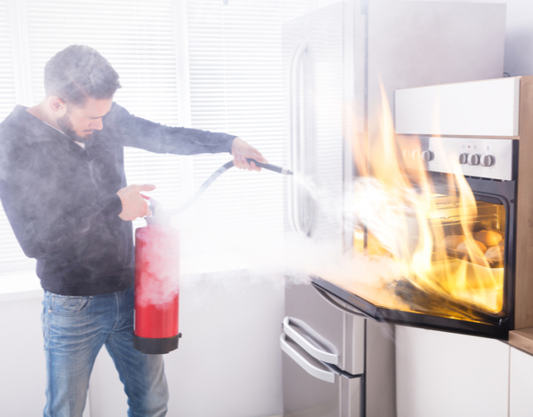 Man using a Fire extinguisher to stop the fire inside the oven