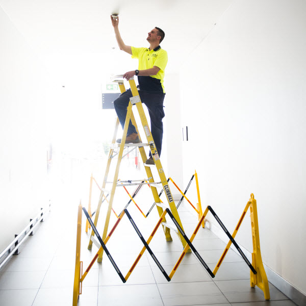 Man installing a fire alarm to the roof