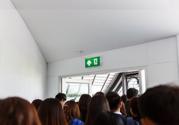 People on their way out to door with a sign of emergency exit