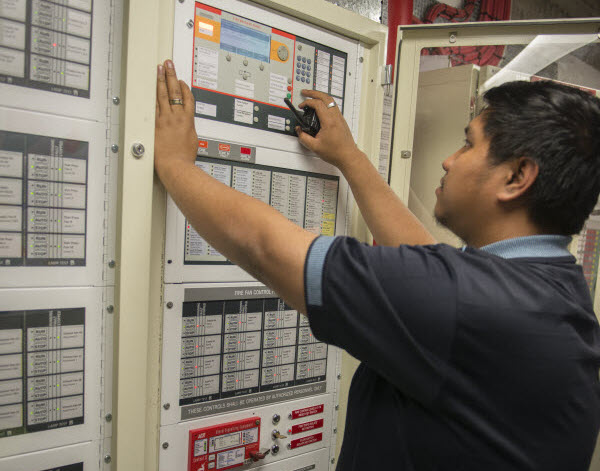 Man checking the main control of fire detector