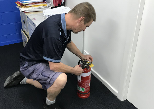 Man holding a Fire Extinguisher on the ground
