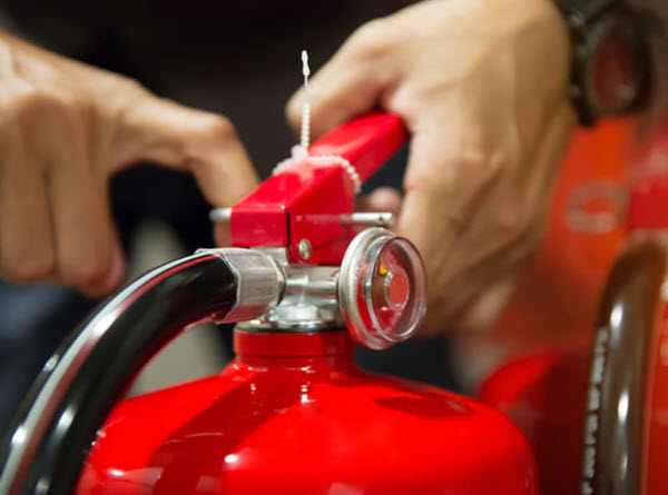 DEM-a man-pulling-the-pin-of-Fire-extinguisher