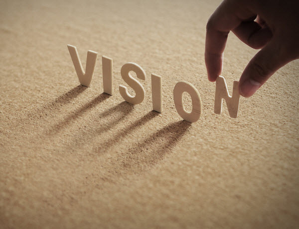 Wooden VISION word and a shadow of a hand holding the letter N