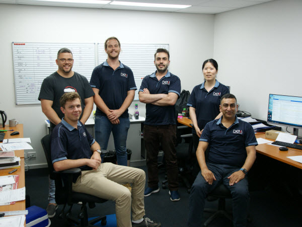 Employees wearing uniform smiling at the camera while inside the office