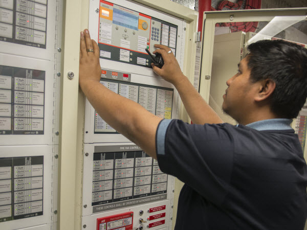 Man checking the fire alarm control panel